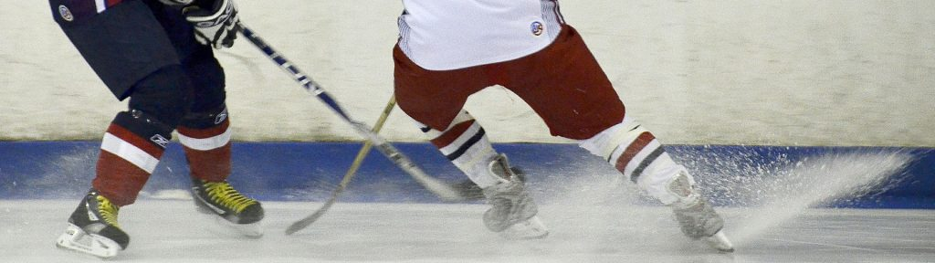 Cropped image of two hockey players going for the puck in the corner